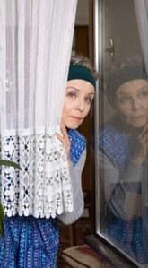 Woman peering around net curtain